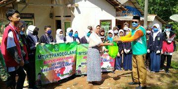 Kepala MTsN 3 Pandeglang H. Eman Sulaeman menyerahkan masker kepada salah seorang warga Cibaliung.