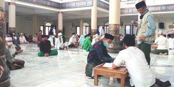 Ketua DMI Kab. Pandeglang H. Abdul Ghaffar sedang melakukan pengecekan data guru ngaji penerima insentif.